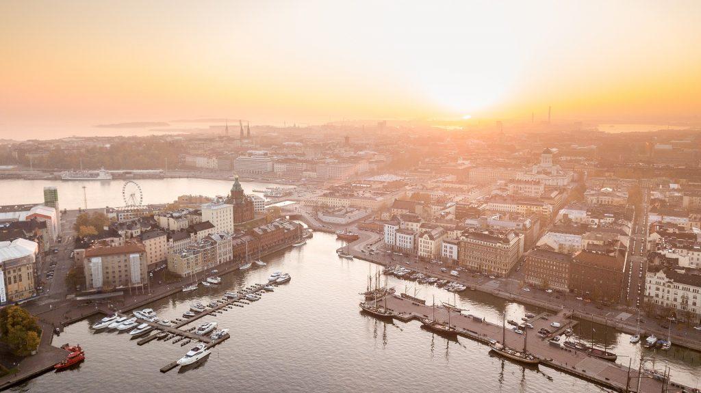Ilmakuva Helsingistä, jonka taivaanranta on värjäytynyt oranssiksi.